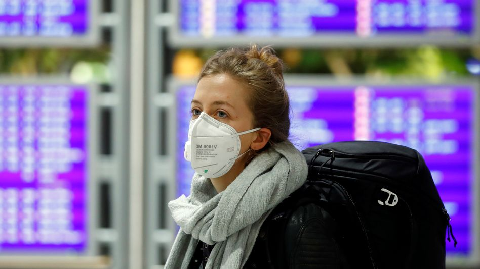 Passagierin mit Schutzmaske am Frankfurter Flughafen