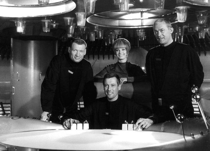 """Die Filmszene von 1965 aus dem Science-Fiction-Klassiker """"Raumpatrouille Orion"""" zeigt (v.l.n.r.) Leutnant Mario de Monti (Wolfgang Völz), Major Cliff Allister McLane (Dietmar Schönherr), Leutnant Tamara Jagellovsk (Eva Pflug) und Leutnant Hasso Sigbjoernson (Claus Holm) in ihrem Raumschiff."""