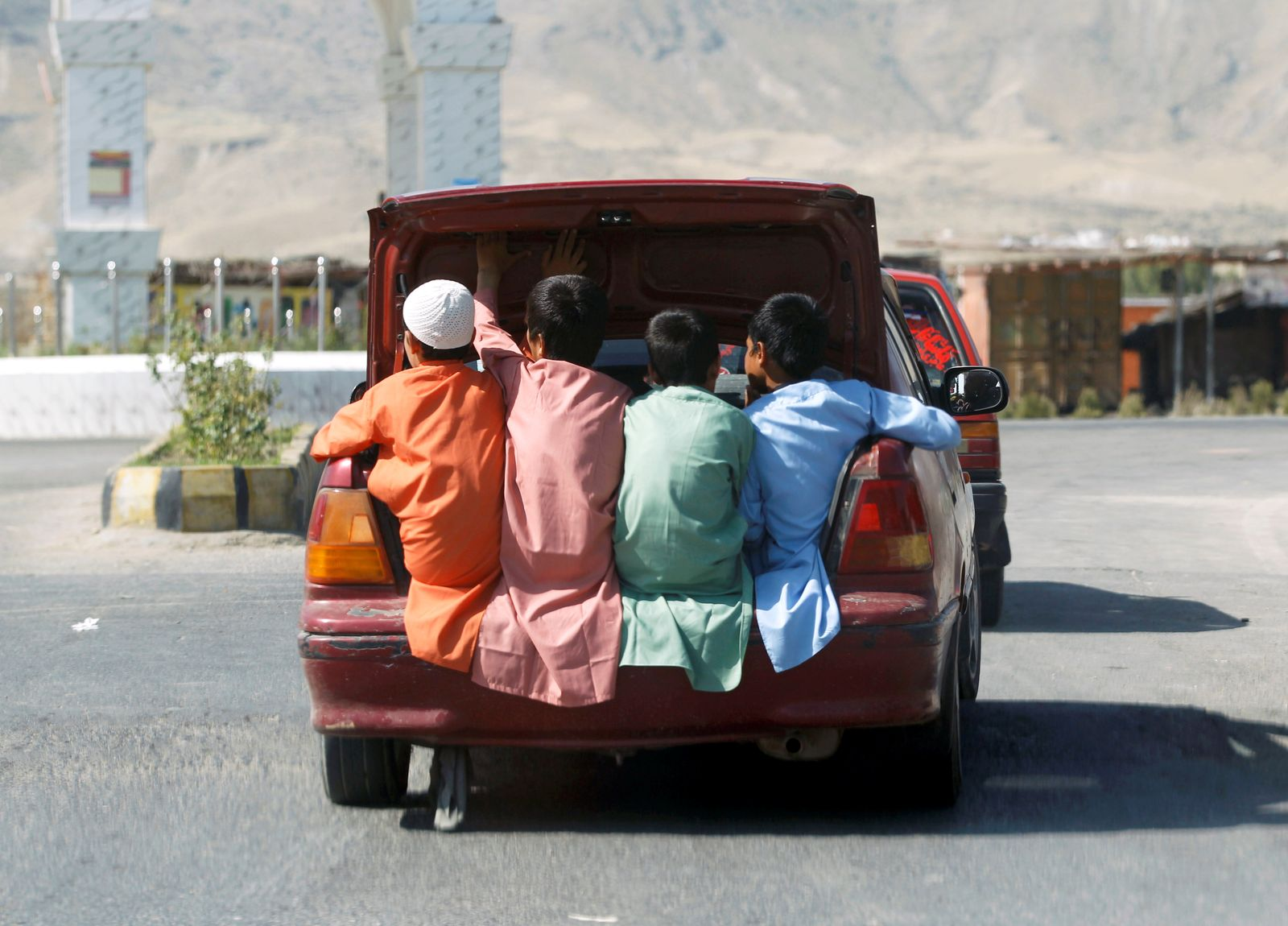Afghan boys travel in the back of a car during Eid al-Fitr, a Muslim festival marking the end the holy fasting month of Ramadan, amid the spread of the coronavirus disease (COVID-19), in Laghman province