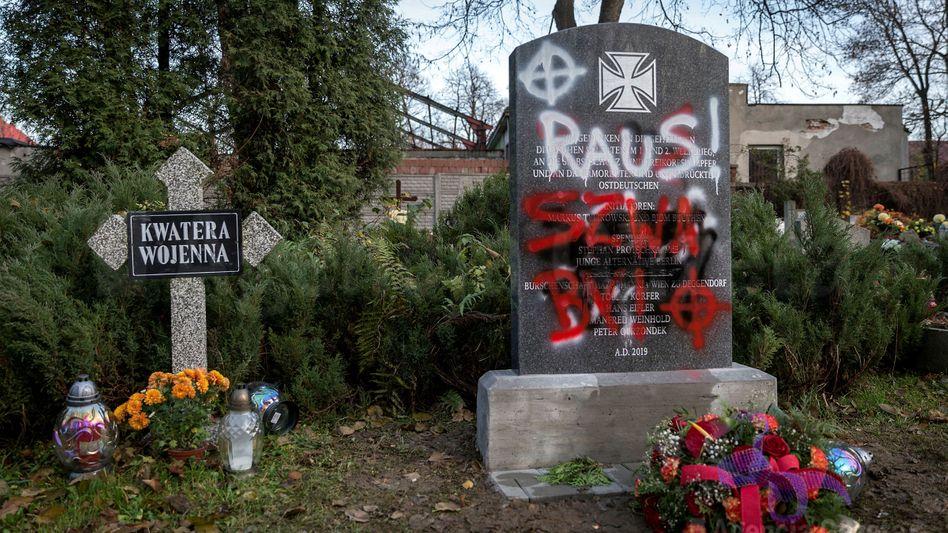 """Beschmierter Gedenkstein auf dem Friedhof in Bytom (Beuthen): """"Deutsche raus"""""""