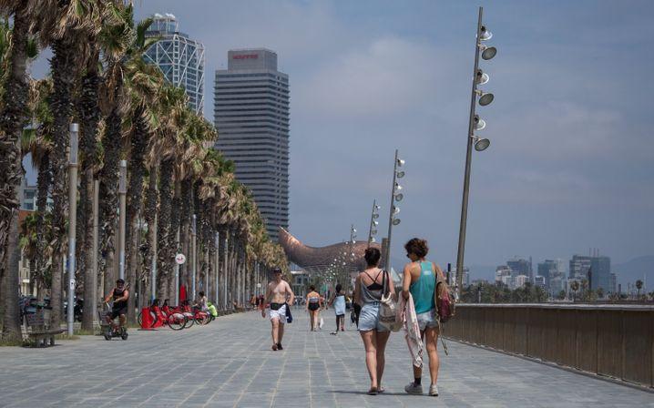 Zwei Frauen spazieren entlang der Strandpromenade in Barcelona. Wegen der stark steigenden Zahl von Corona-Infektionen in Spanien warnt das Auswärtige Amt nun vor touristischen Reisen in drei Regionen des Urlaubslands