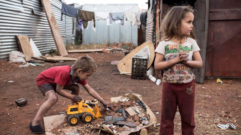 Kinder einer armen Familie spielen vor ihrem Zuhause in einem Vorort von Johannesburg