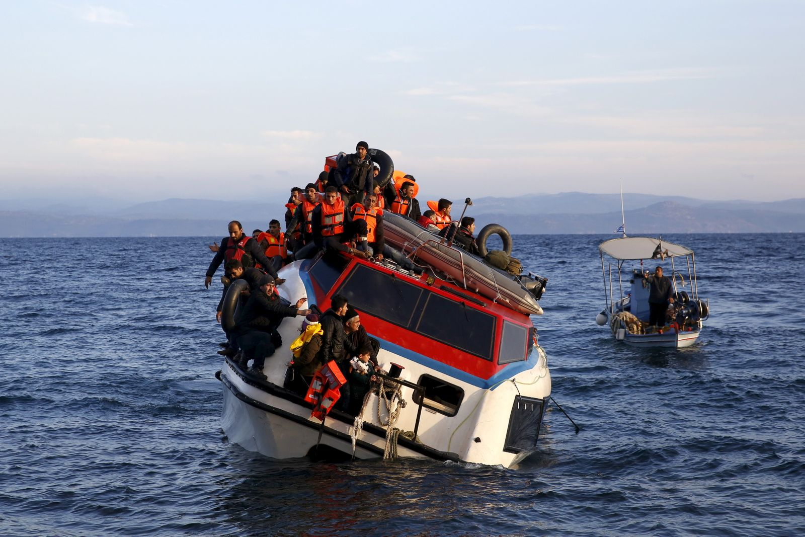 A Greek fishing boat sails next to a half-sunken catamaran carrying around 150 refugees, most of them Syrians arriving after crossing part of the Aegean sea from Turkey, on the Greek island of Lesbos