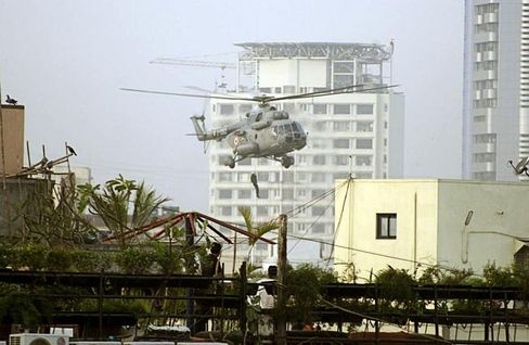A National Security Guard commando rappels from a helicopter near the Jewish center in Colaba district.
