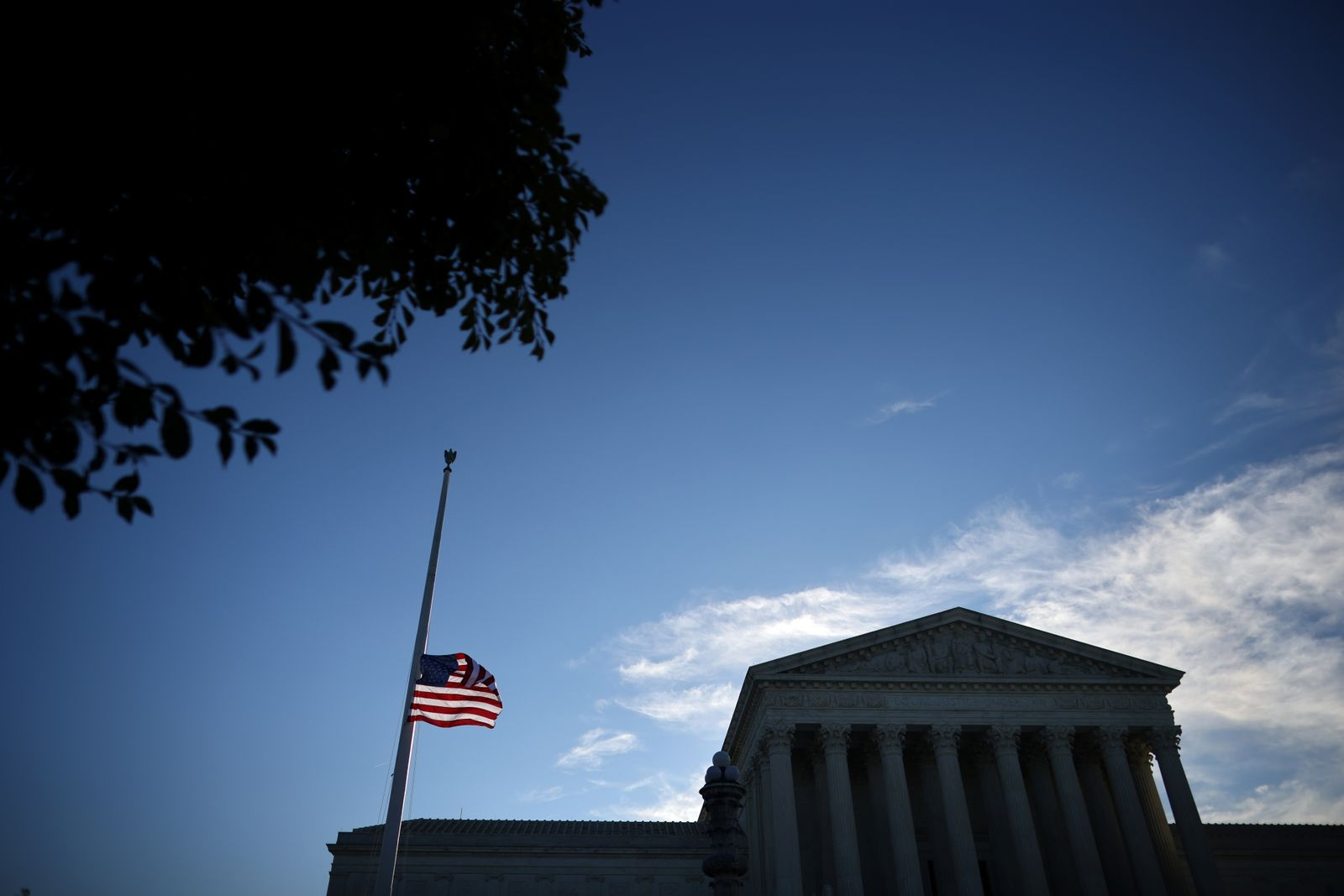U.S. flag is seen at half mast as people gather in front of the U.S. Supreme Court following the death of U.S. Supreme Court Justice Ruth Bader Ginsburg, in Washington