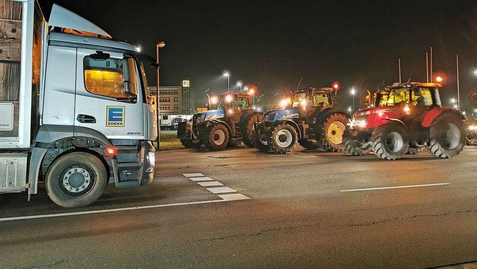 Bauern blockieren mit ihren Traktoren einen Edeka-Laster vor einem Großlager der Kette nahe Oldenburg