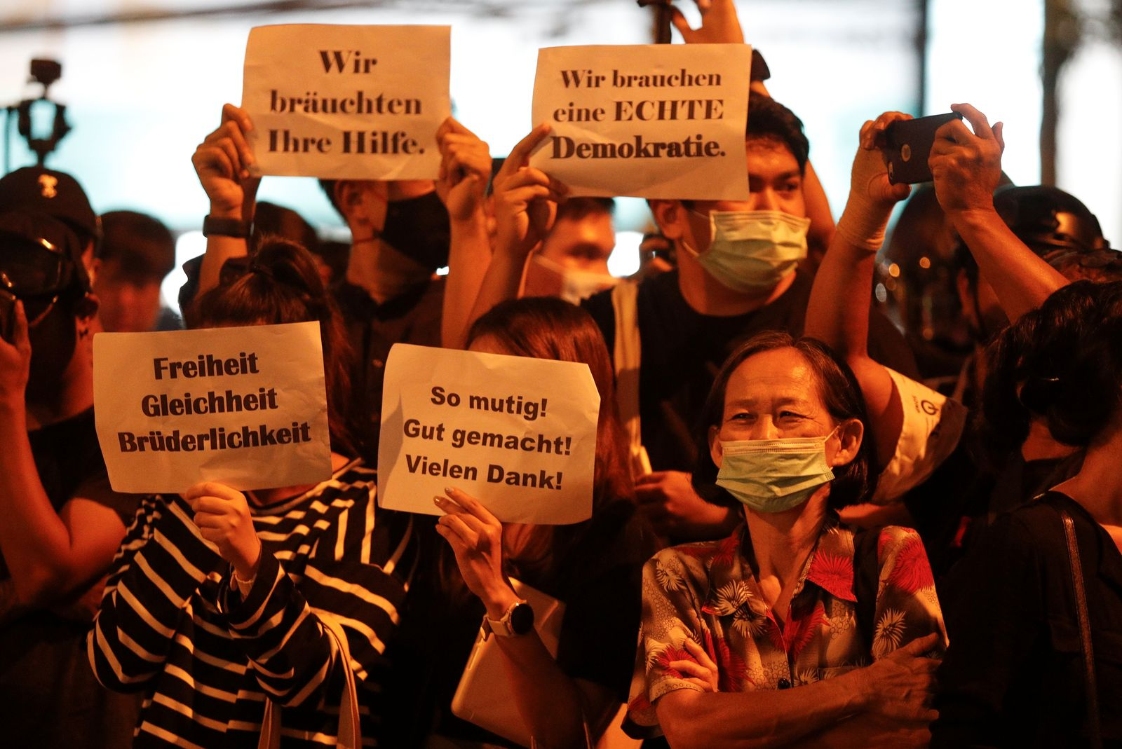 Pro-democracy demonstrators hold placards as they protest outside the German Embassy, in Bangkok