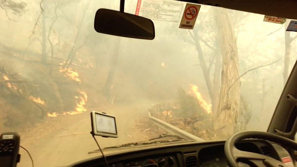 Ein Feuerwehrfahrzeug bahnt sich einen Weg durch die Flammen in New South Wales