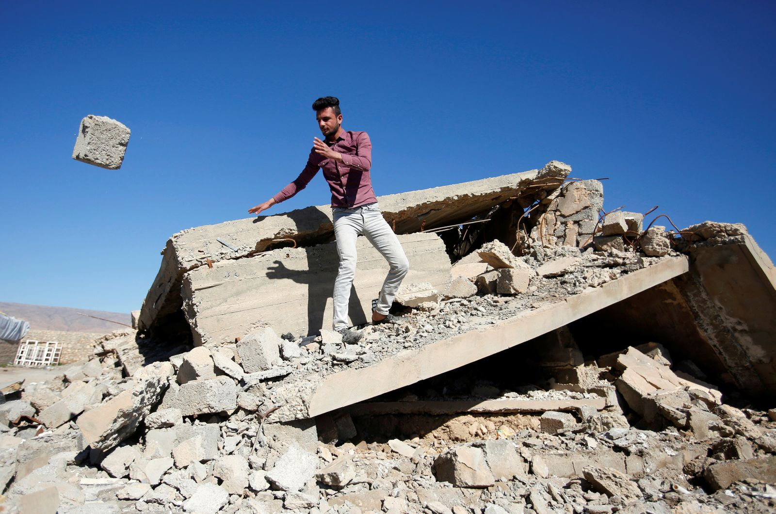 Yazidi man raises the rubble of his damaged house, which was destroyed by Islamic State militants near Sinjar