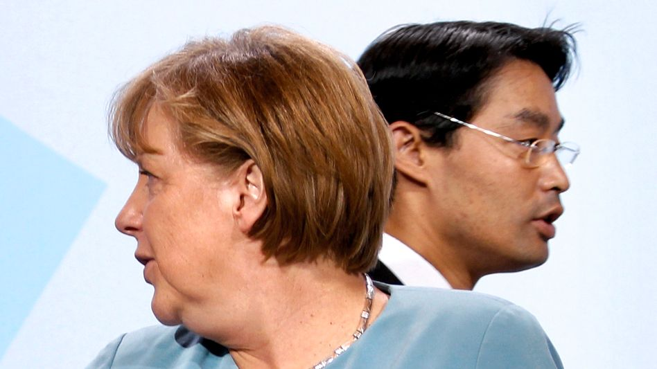 At odds: German Chancellor Angela Merkel (L) and Economy Minister Philipp Rösler, the leader of the pro-business FDP party.