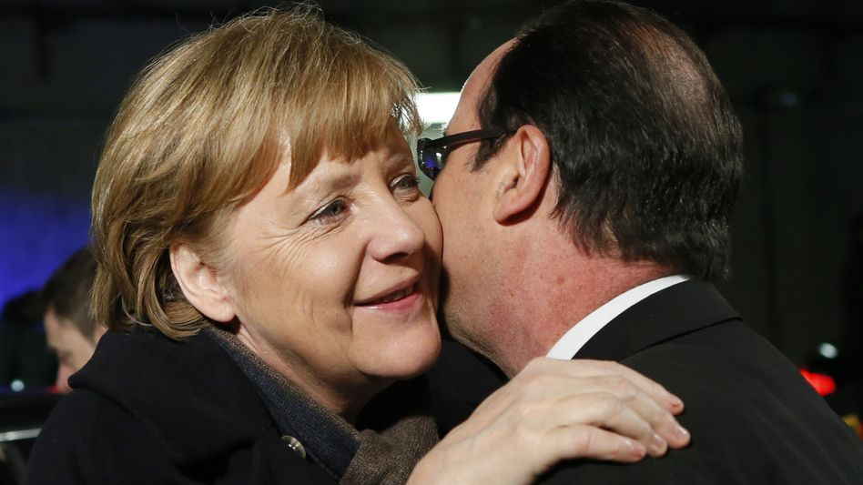 France's President François Hollande welcomes German Chancellor Angela Merkel at a friendly international football match between France and Germany on Wednesday.