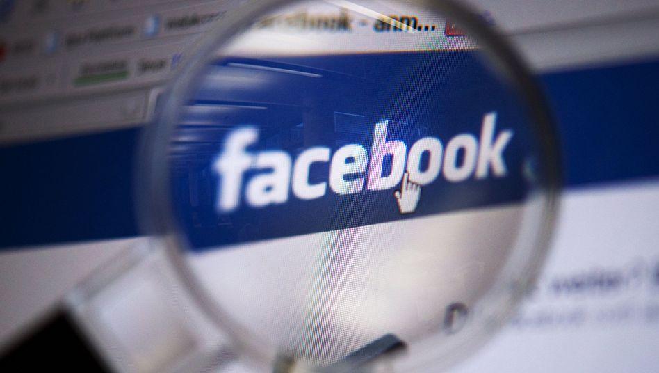 Website von Facebook durch eine Lupe: Einige Leute sind jetzt echt sauer