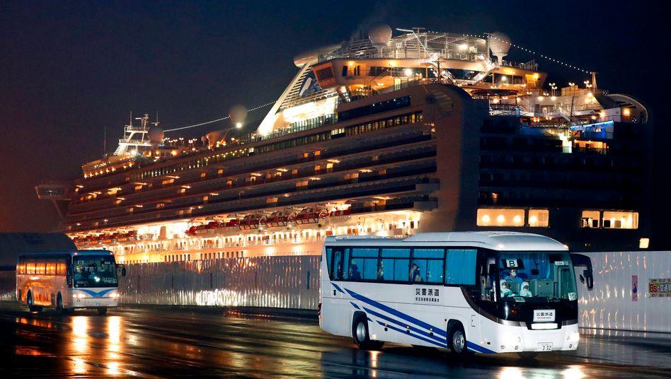 """Busse mit US-Bürgern verlassen den Hafen von Yokohama - im Hintergrund ist das unter Quarantäne stehende Kreuzfahrtschiff """"Diamond Princess"""" zu sehen"""