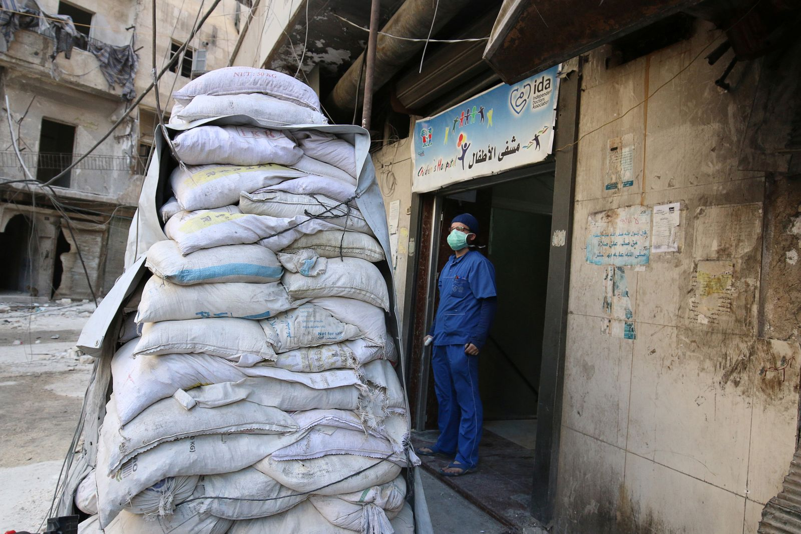 A medic stands behind sandbags in the damaged al-Hakeem hospital, in the rebel-held besieged area of Aleppo