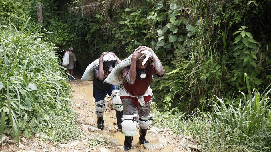 Goldschürfer schleifen Säcke voller Sediment im Osten Kongos: Der Schmuggel boomt