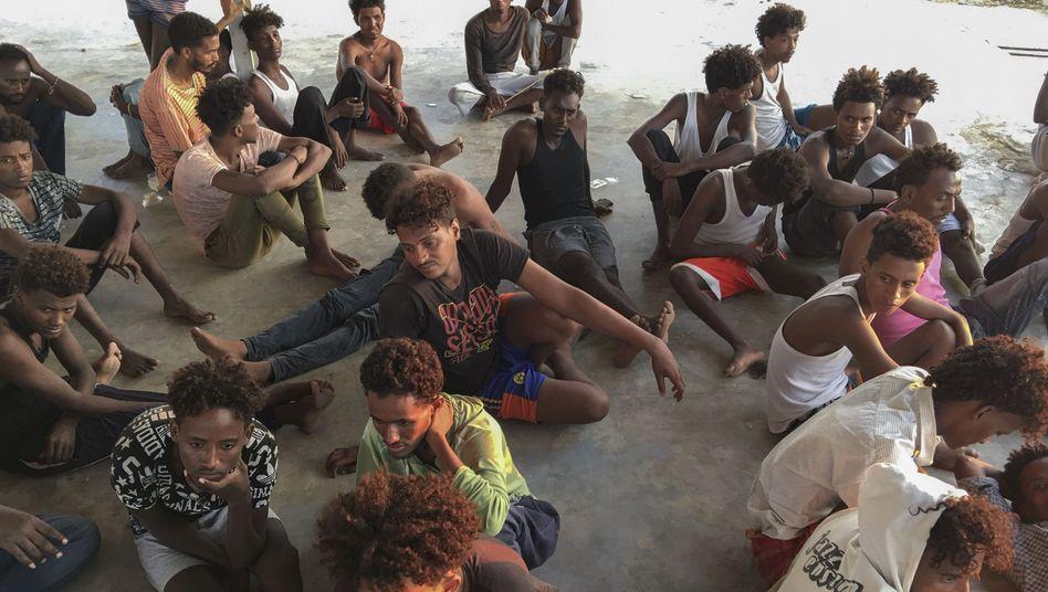 Gerettete Migranten sitzen an der Küste etwa 100 Kilometer östlich von Tripolis