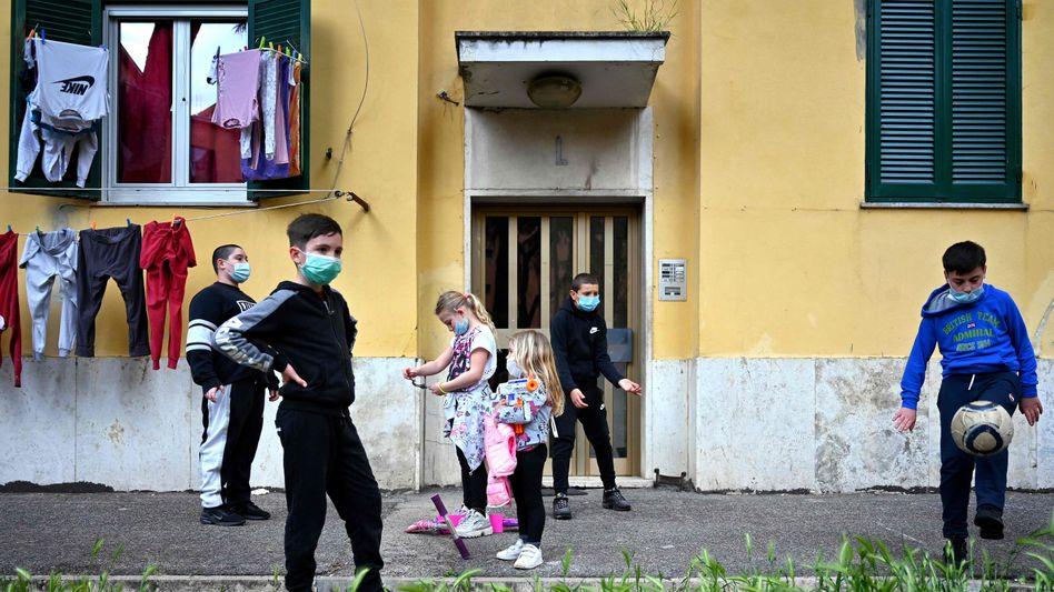 Spielende Kinder mit Mundschutz in Rom: Reale Gefahr