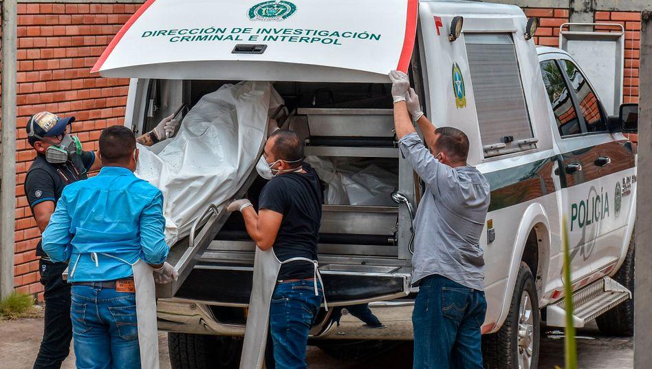Polizeibeamte verladen Körper von Opfern der Massaker