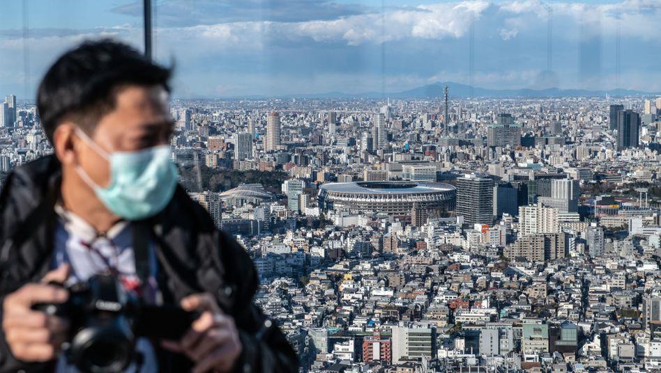 Mann mit Kamera, im Hintergrund: das Neue Nationalstadion in Tokio