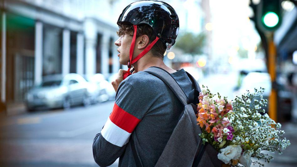 Mann mit Fahrradhelm: Radelt man mit Helm risikofreudiger als ohne?