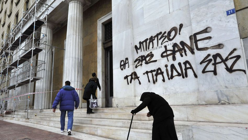 An eldery woman begs outside the Bank of Greece headquarters in Athens in February.