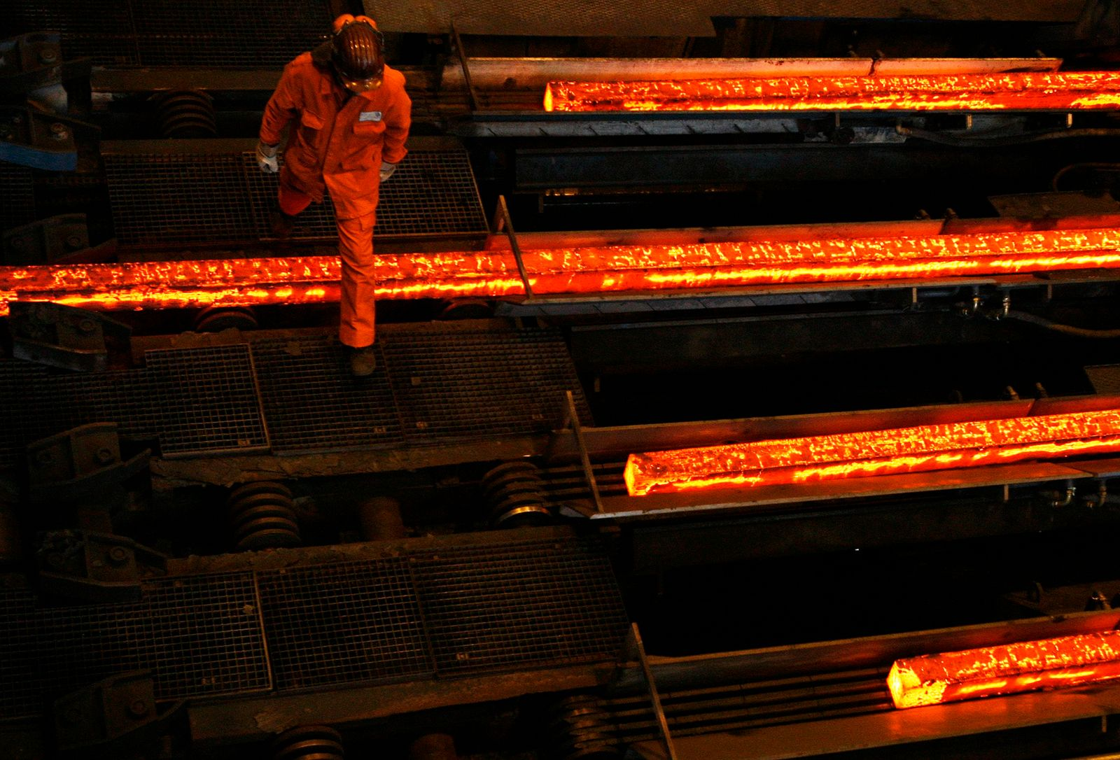 A labourer walks over hot steel plates at the factory of Swiss Steel AG which is partly owned by the 'Schmolz + Bickenbach' group in Emmenbruecke, outside Lucerne