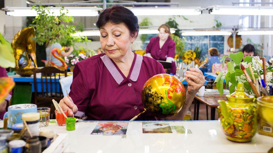 Chochloma-Malerei ist typisch russisches Handwerk, goldfarbene Schalen und Löffel werden mit filigranen Motiven verziert. Diesen Job macht Tatiana Kalinina - zur WM bemalt sie sogar Fußbälle.