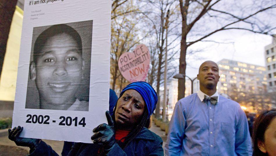 Demonstrantin mit einem Bild von Tamir Rice 2014