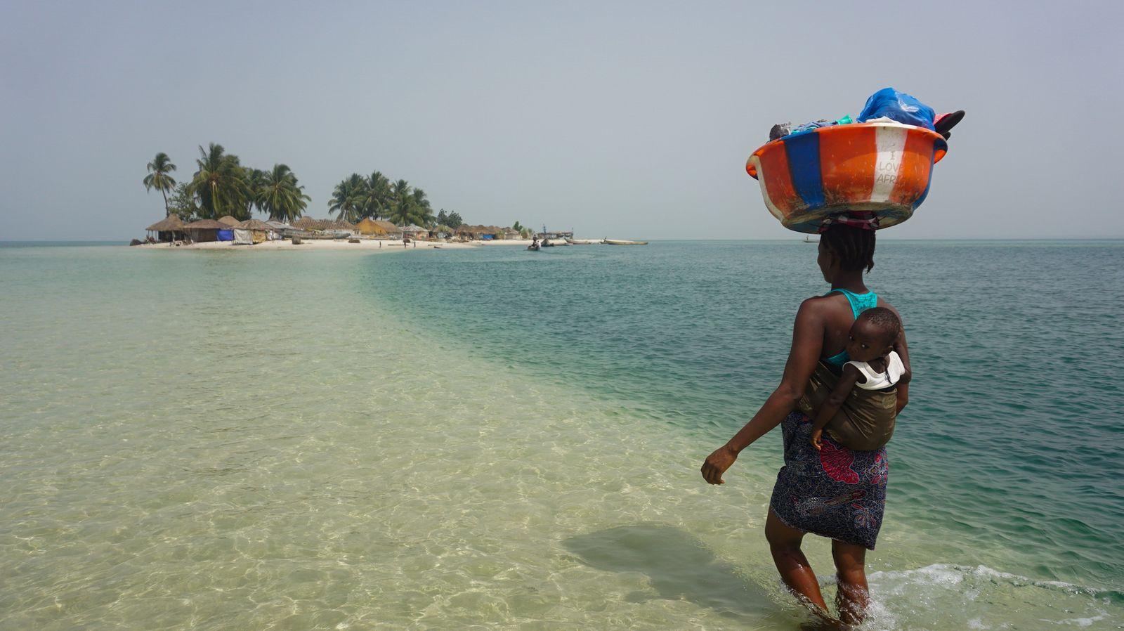 Nyangai. Eine Frau wartet durch das Wasser von der einen Seite der Insel zur anderen. In etwa fünf Jahren wird von der Insel kaum noch etwas übrig sein - Saidu Bah (2)