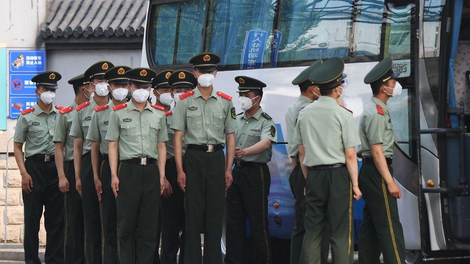 Paramilitärische Polizei sperrt den Markt in Peking ab, von dem der erneute Ausbruch ausgegangen sein soll