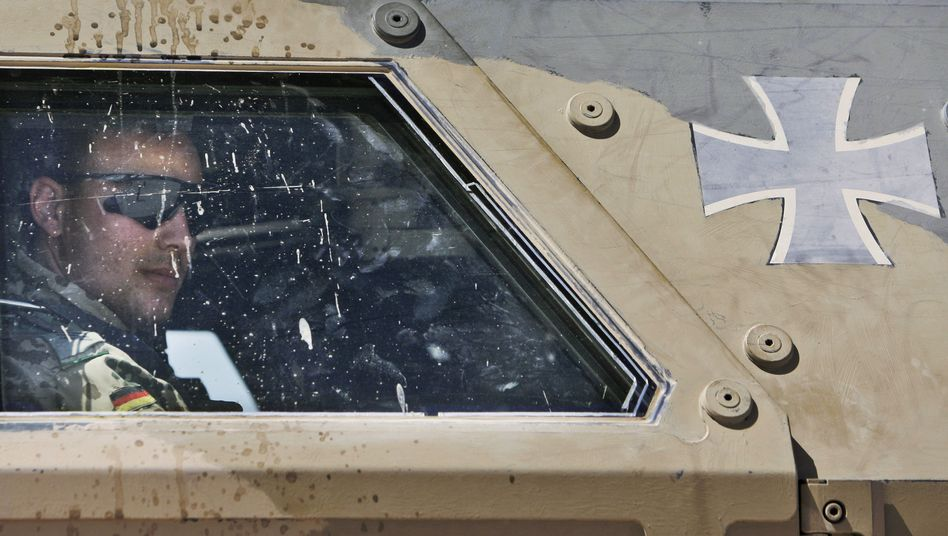 A German ISAF soldier looks out of an armored vehicle as he leaves for Afghanistan.