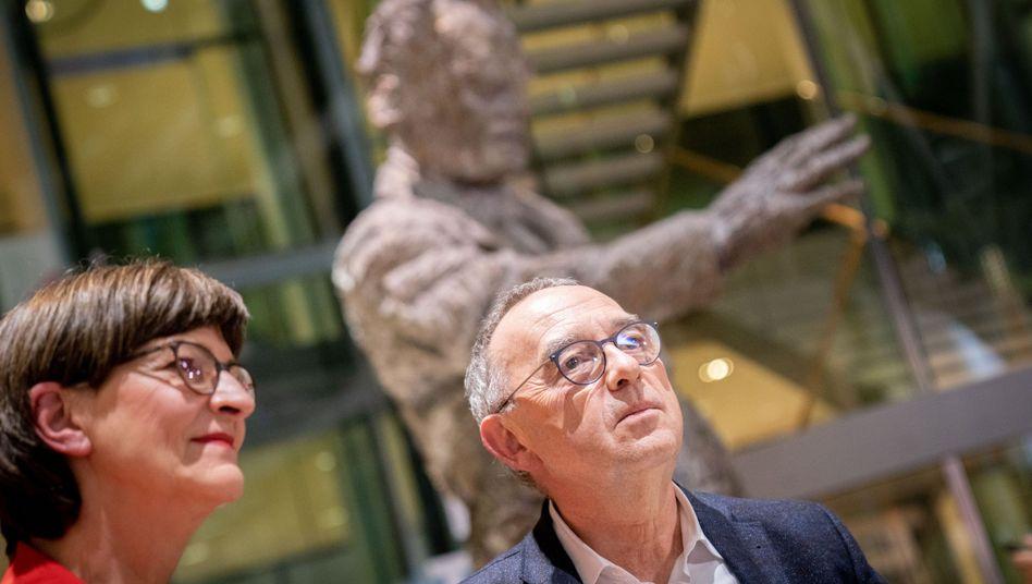 Saskia Esken und Norbert Walter-Borjans vor der Statue Willy Brandts in der SPD-Zentrale