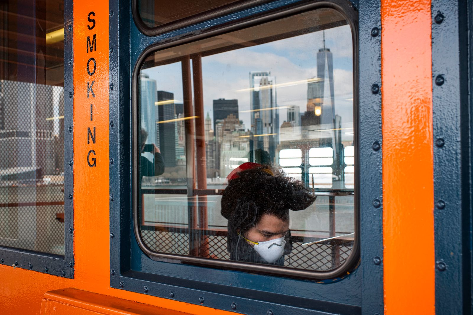 A passenger wears a face mask on the the Staten Island Ferry in New York, March 16, 2020. (Joshua Bright/The New York Times)