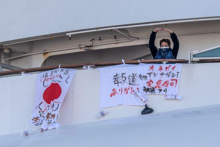 """Hilferuf von der """"Diamond Princess"""" vor Yokohama: Bitte filmt das, die Medikamente werden knapp, steht auf dem Banner"""