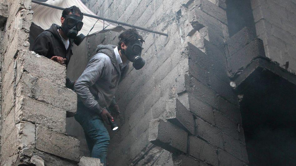 Gasmaskenträger in Aleppo: Nach einem Bombenangriff suchen Zivilisten in den Trümmern nach Überlebenden