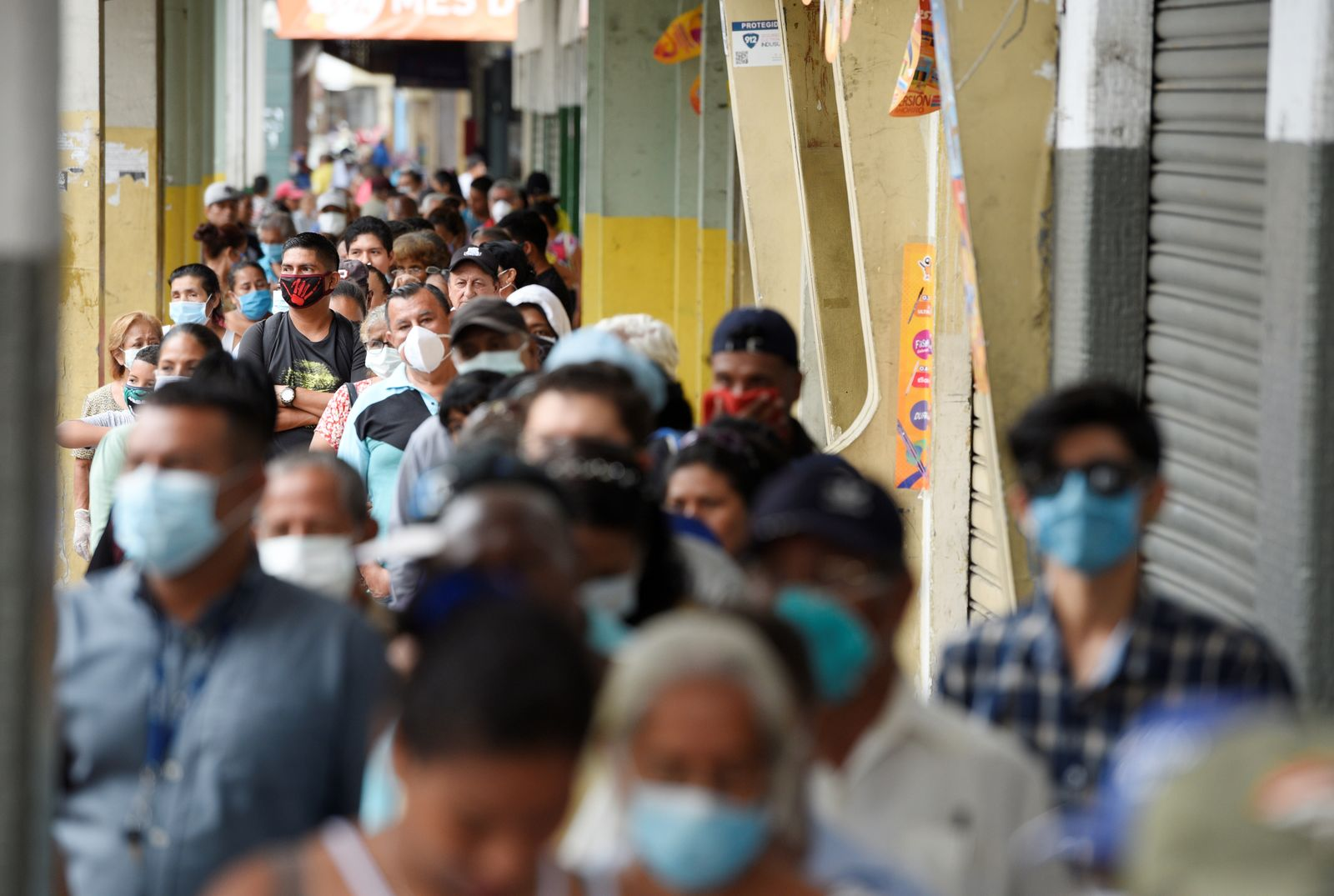 Elderly stand in line to collect their monthly pension before the 4:00 pm - 8:00 am curfew imposed by the government to prevent the spread of the coronavirus disease (COVID-19), in Guayaquil