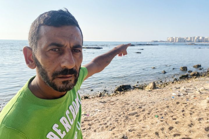 """""""Da vorne werden sie abgeholt"""", zeigt Rabie Nakhal am Strand von Tripoli"""
