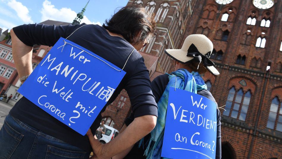 """Zwei Demonstratinnen tragen bei einer Demo in Stralsund Schilder mit den Aufschriften: """"Wer manipuliert die Welt mit Corona?"""" und """"Wer verdient an Corona?"""""""
