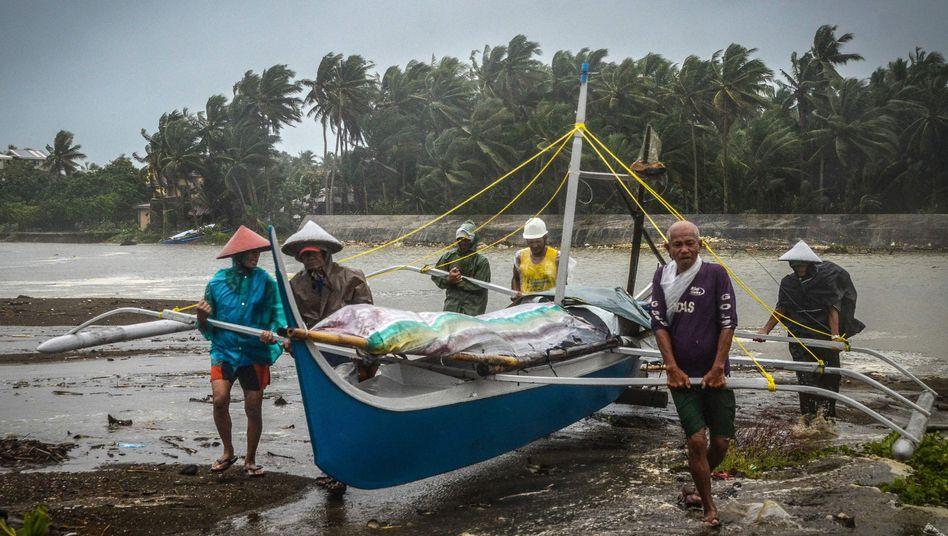 Fischer in der Provinz Eastern Samar tragen eilig ein Boot aus dem Wasser - der Taifun kommt näher