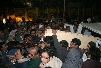 Supporters of Pakistan's assassinated opposition leader Benazir Bhutto unload her coffin from an ambulance at her ancestral house.