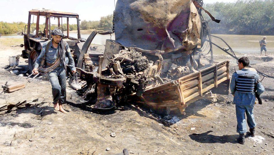 Nach dem Bombardement: Afghanische Polizei inspiziert einen zerstörten Tanklaster