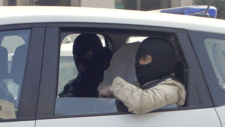 Polizisten, Verdächtiger: In der Mitte sitzt vermutlich der Bruder des Attentäters Merah