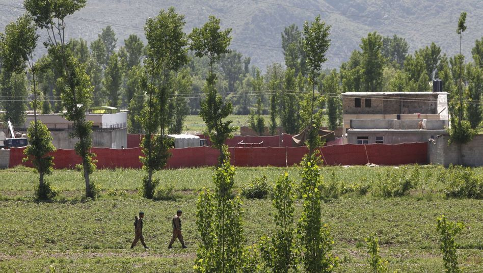 Pakistani soldiers walk past a compound, surrounded in red fabric, where it is believed that US forces killed Osama bin Laden.