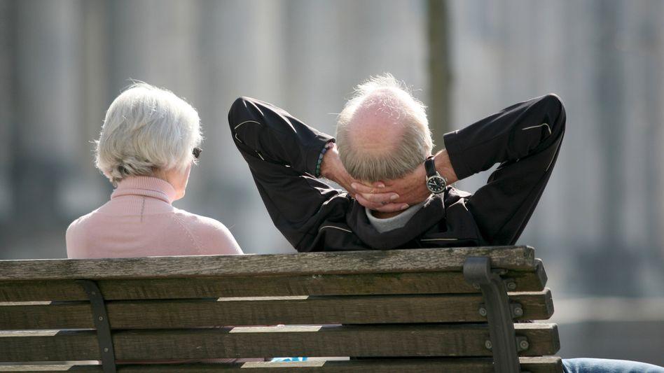 Rentner ruhen sich in Berlin auf einer Bank aus