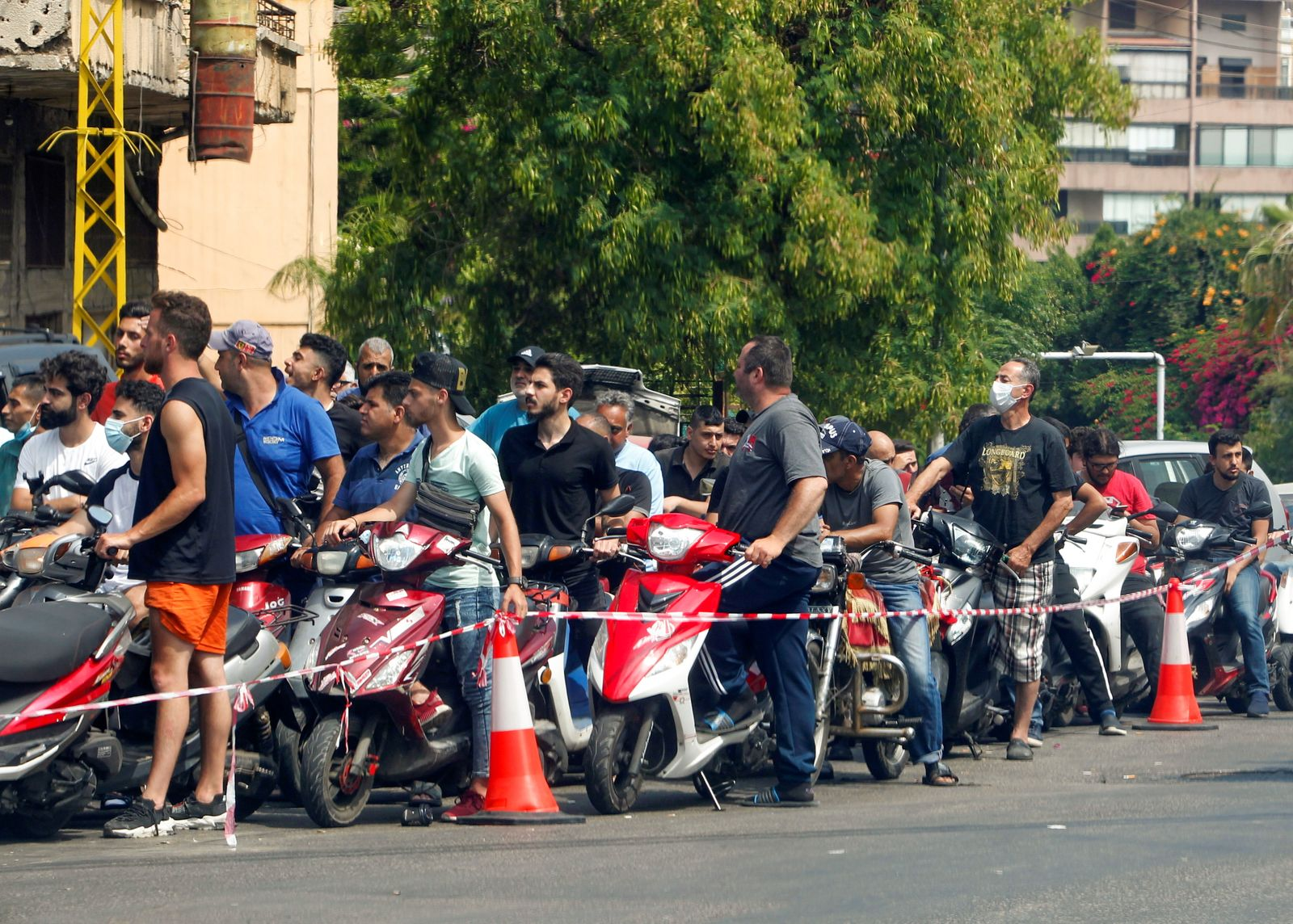 Motorbike drivers wait to get fuel at a gas station in Beirut