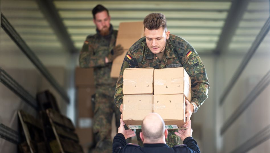 Soldaten und Feuerwehrmänner verladen Kartons mit Schutzkleidung (Foto vom 22. März): Bundeswehr stellt sich auf Unterstützung für zivile Behörden ein