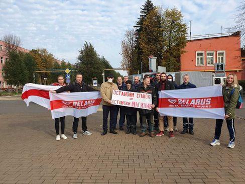 Michail Gromow (M., hält das Schild, schaut nach rechts), mit Kollegen