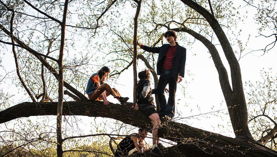 Jugendliche sitzen auf einem Baum am Weißensee, Berlin