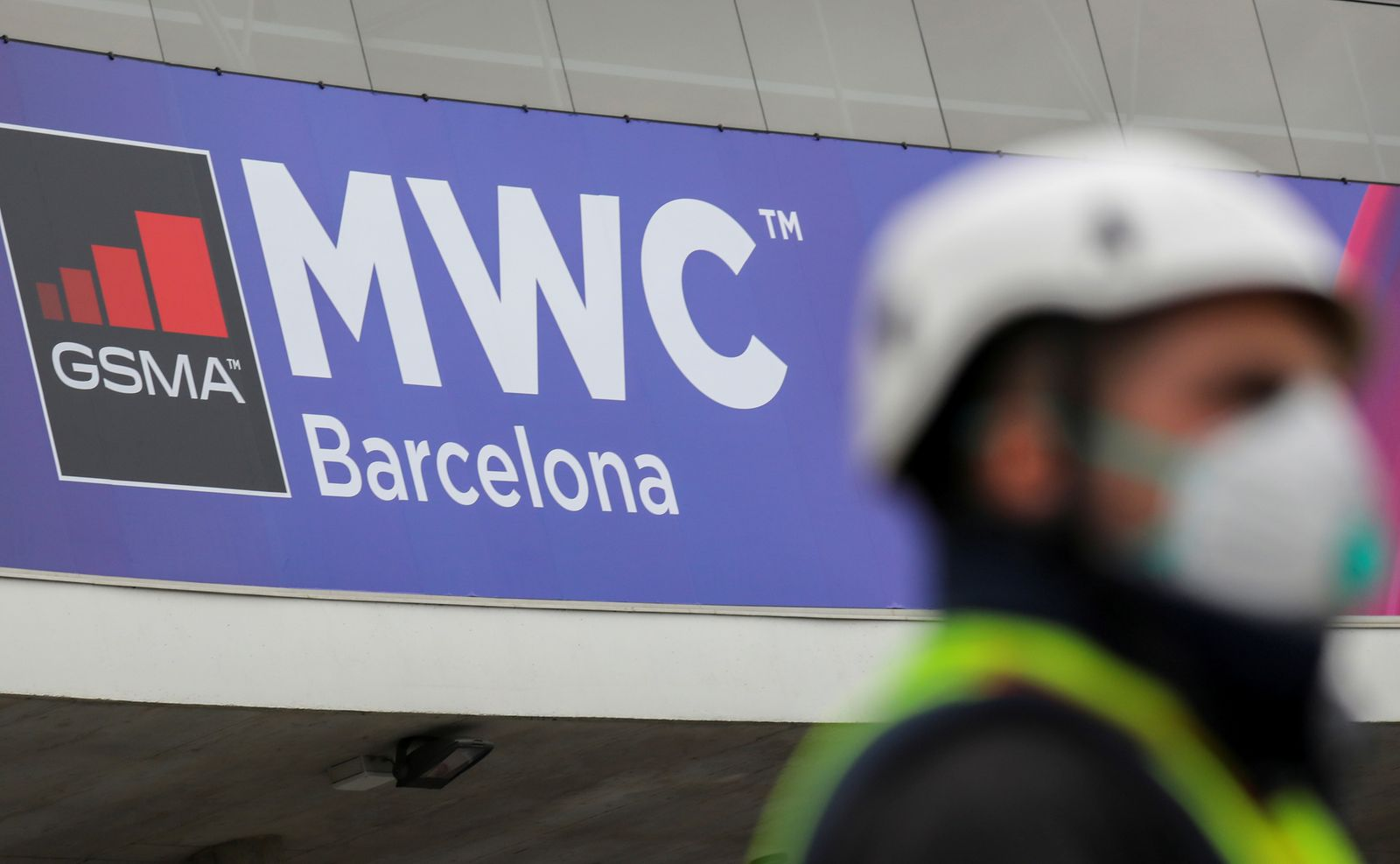 FILE PHOTO: Employee is pictured next to the logo of the cancelled event MWC20 (Mobile World Congress) in Barcelona