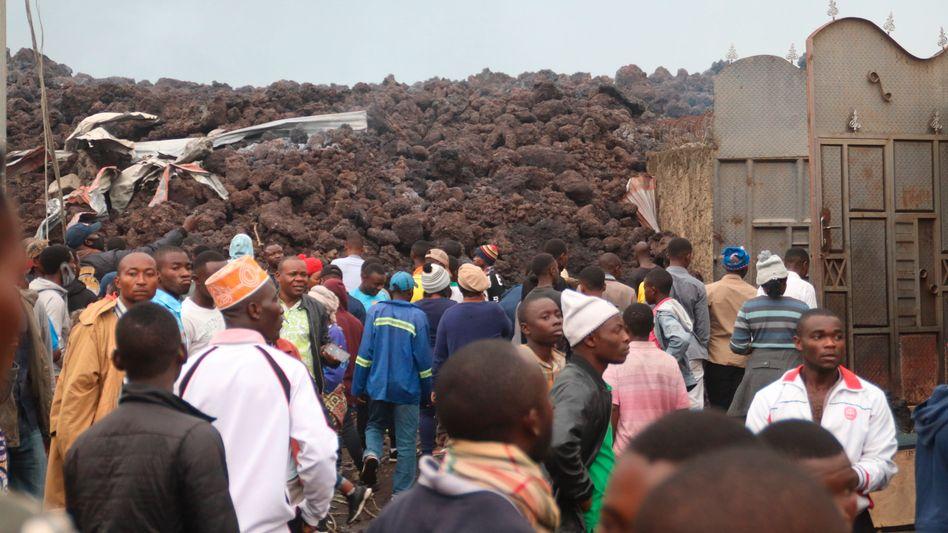 Anwohner betrachten die von einem Lavastrom angerichtete Verwüstung in einem Vorort von Goma